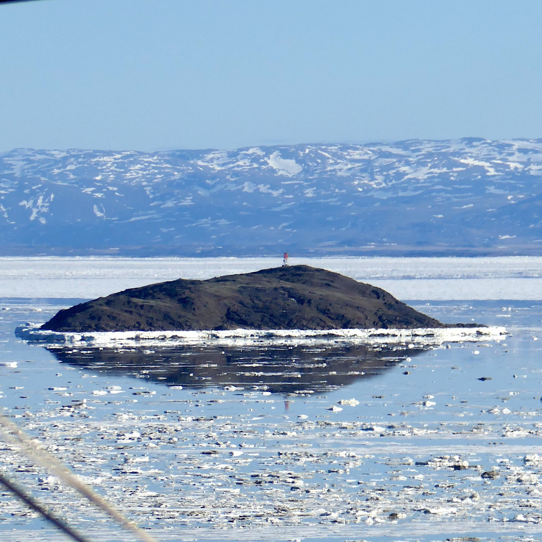 Island in the sea ice, surrounded by reflecting water on the surface; June 18, 2019
