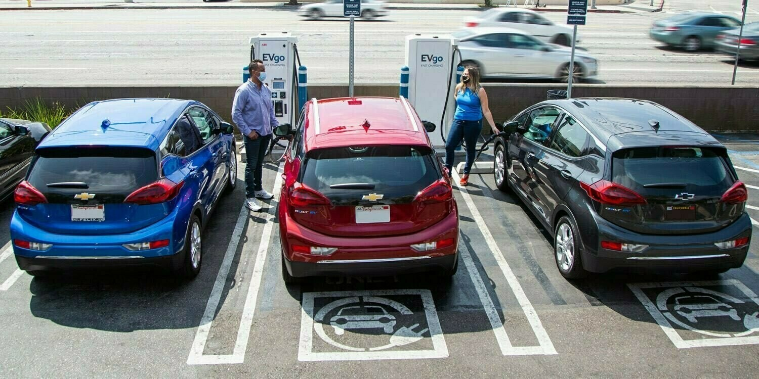 """GM promo picture of people """"refueling"""" their EVs hanging onto the """"nozzle""""!  (probably ©GM)"""